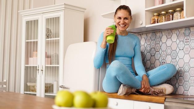 한 여성이 스포츠 영양이나 물을 위한 녹색 병을 들고 부엌의 조리대에 앉습니다. 건강한 라이프 스타일 개념입니다.