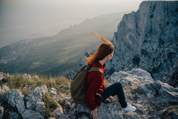 Женщина сидит на краю обрыва, турист-путешественник смотрит на закат
