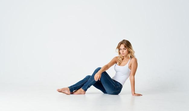 女性はジーンズとtシャツの明るい背景の床に座っています
