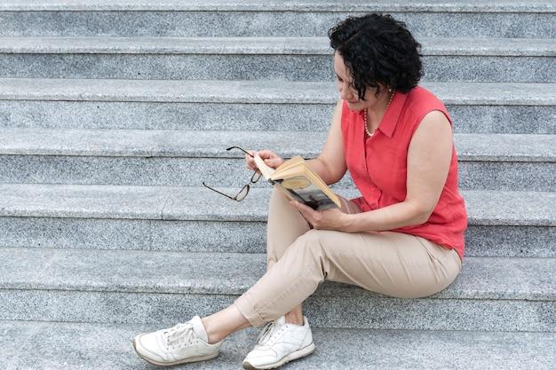 街の階段に座って本を読む女性。