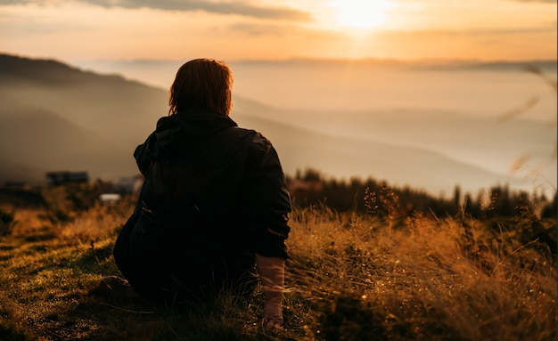 여자는 태양이 상승하기를 기다리는 산 꼭대기에 앉아있다.