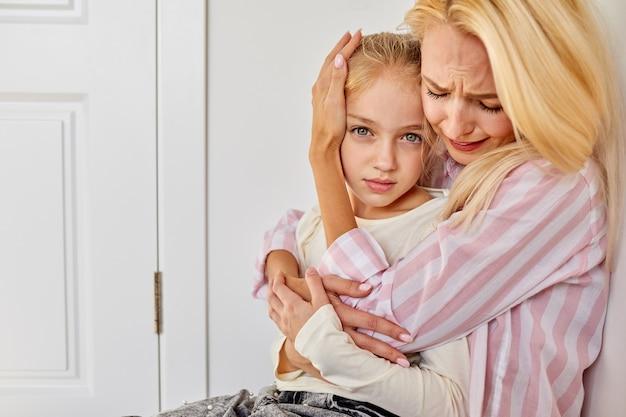 女性は子供と一緒に座って、男性が子供に誓う間、彼女を落ち着かせます