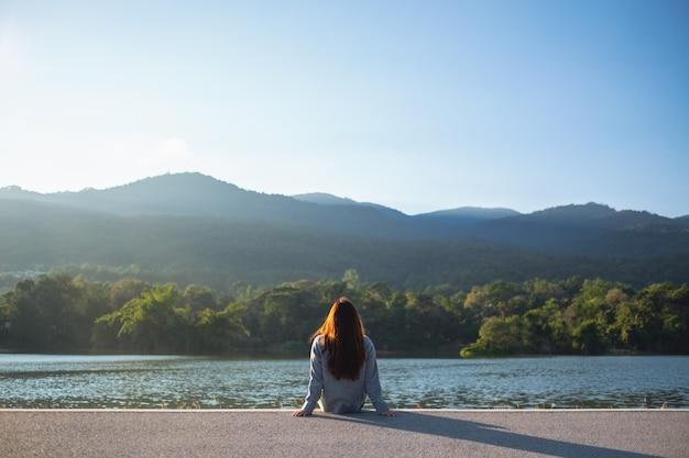 Женщина сидит в одиночестве у озера, глядя на горы на зеленом фоне природы
