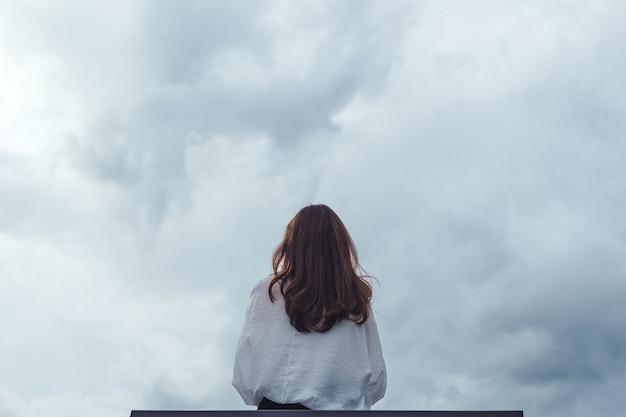 Женщина сидит в одиночестве на деревянной скамейке в парке с облачно и мрачно