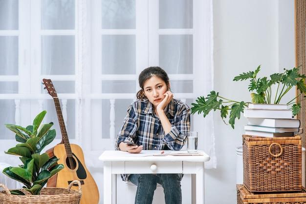 Женщина, сидящая за столом, анализирует документ и испытывает стресс.