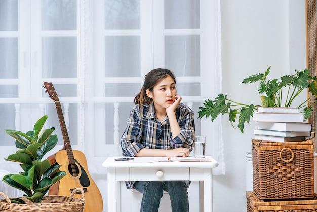 机に座っている女性が文書を分析し、ストレスを感じています。
