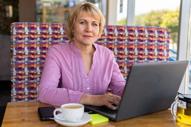 카페에서 일하는 노트북과 차 한 잔을 들고 테이블에 앉아 있는 여성