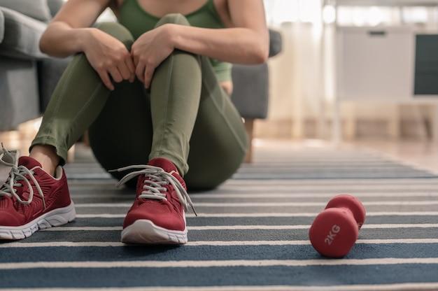 休息運動のために座っている女性検疫運動トレーニング中に屋内で運動する