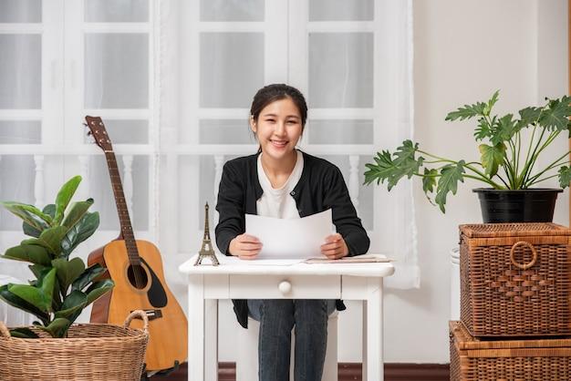 Женщина, счастливо сидящая за столом, анализирует документы.