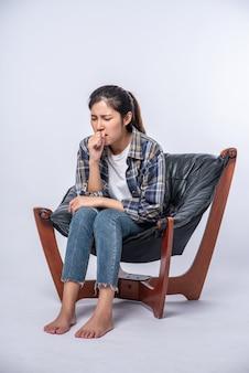 Женщина сидит в кресле с болью в животе и прижимает руку к животу