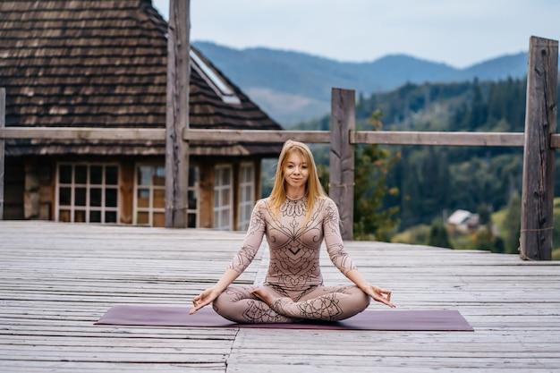Женщина сидит в позе лотоса на утро на свежем воздухе.