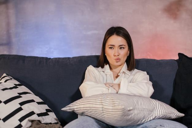 Женщина сидит на диване в уютной комнате смотрит телевизор и расстроена тем, что видит на экране