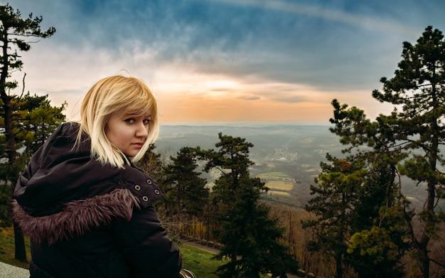 Женщина, сидящая на краю лесных ворот, наслаждаясь прекрасным видом на горный пейзаж на закате