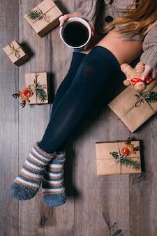包まれたプレゼントで床に座っている女性