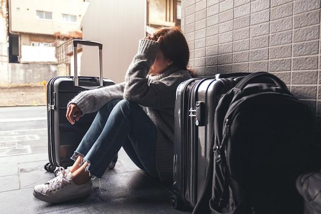Женщина сидит с грустью и потерянной во время путешествия с большим количеством вещей на полу