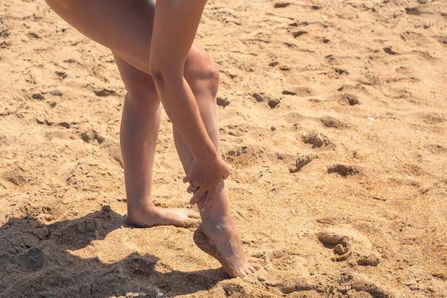 女性は、日焼け止めを使って足を日焼け止めで塗ります。海で日光浴。