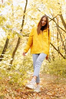 秋に女性が笑顔で森の中を歩く