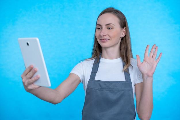 화상 통화 중에 미소를 지으며 태블릿 웹캠을 흔드는 여성