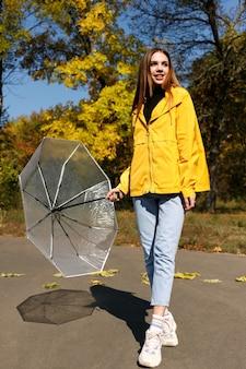 散歩中の秋、傘をさして笑顔を浮かべる女性。閉じる。秋