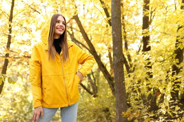 10月の黄色い紅葉の前で黄色い秋のジャケットを着た女性が微笑む。テキスト用の空き容量