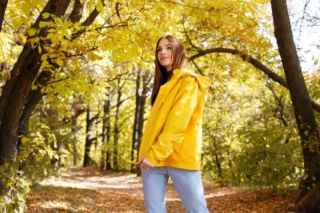 自然の中を散歩中の紅葉を背景に黄色いレインコートを着て微笑む女性