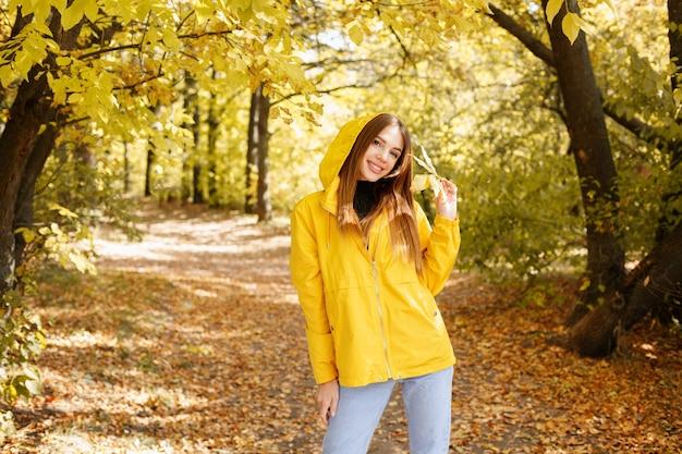 秋の黄色い森の前に黄色い葉が付いた秋の黄色いレインコートを着た女性が微笑んでいます。秋