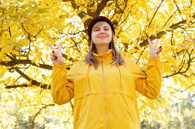 秋の黄色い木の前で女性が微笑む。秋の気分
