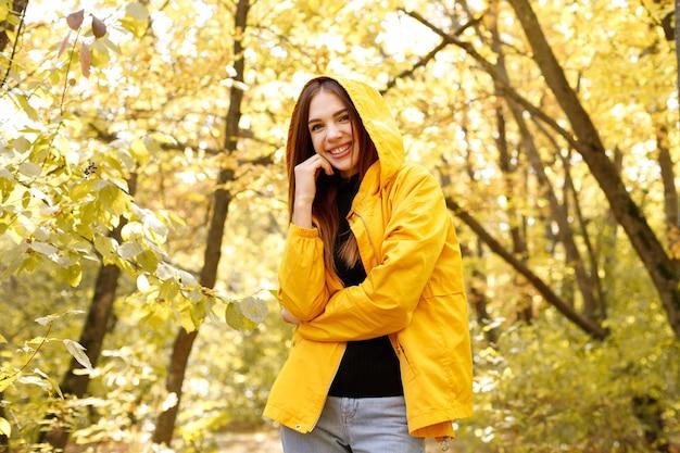 女性は黄色の秋の背景に微笑む