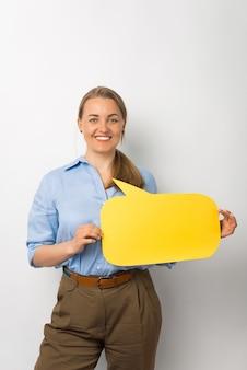 Женщина улыбается в камеру с желтым речевым пузырем