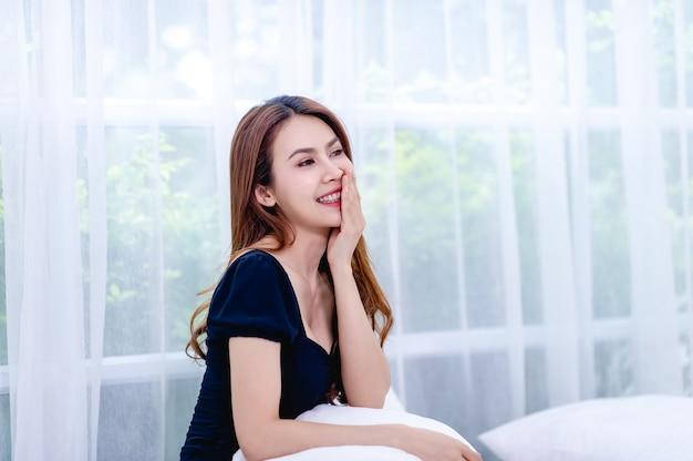 Женщина счастливо улыбается в белой спальне