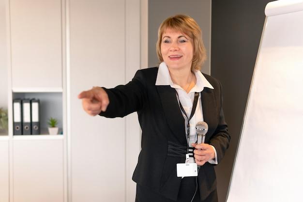 한 여성이 사무실에서 이야기합니다. 비즈니스 라운지에서 중년 여성이 상담을 진행하고 있다. 그녀는 훈련을 한다.