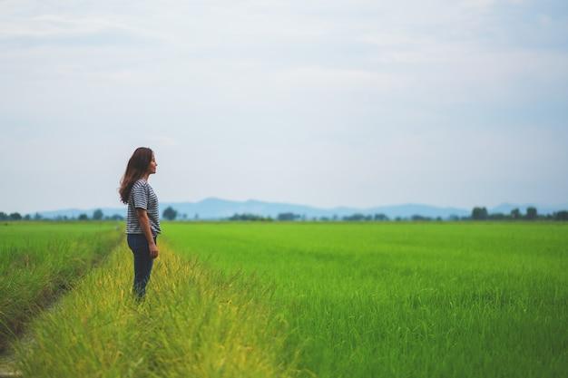 편안하고 차분한 느낌으로 서서 아름다운 논을 바라보는 여성