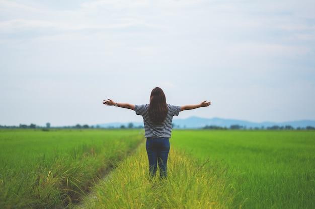 편안하고 신선한 느낌으로 아름다운 논에 서서 팔을 뻗는 여성