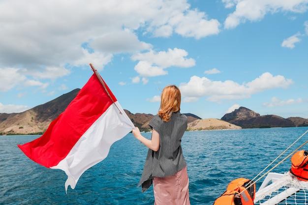 보트에 서서 바다 한가운데에서 인도네시아 국기를 흔드는 여성