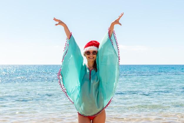 산타 모자를 쓰고 하늘까지 손으로 해변에 서있는 여자