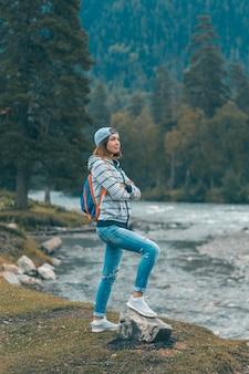 女性が川のそばに立ち、山を眺めている。山麓でのハイキング。