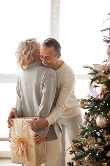Женщина стоит возле елки и прячет за спиной подарок мужчине