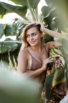 島の緑のバナナの葉の近くに女性が立っています。熱帯の木