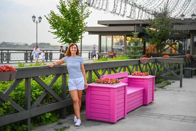 한 여성이 카잔 제방에 꽃이 만발한 분홍색 벤치 옆에 서 있습니다. 여름 휴식입니다.