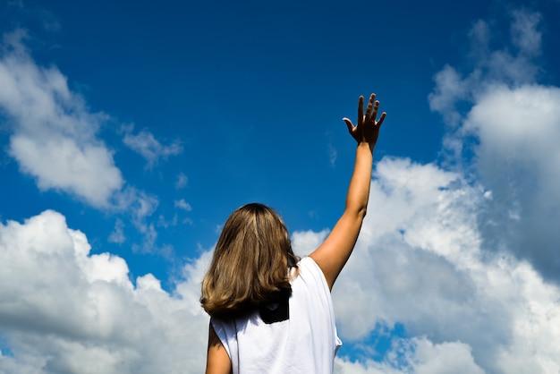 Женщина в белой футболке стоит спиной к фотографу на фоне голубого неба с облаками. протягивает руку к небу.