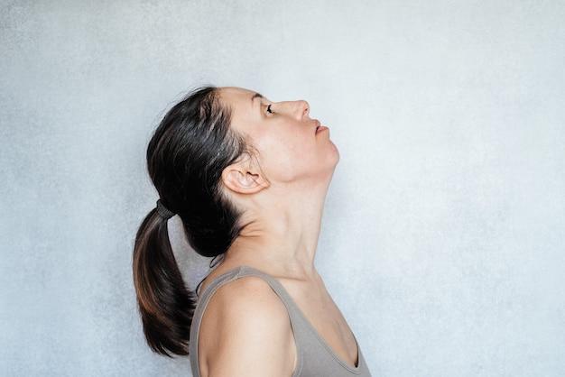 Mckenzie 방법을 사용하여 목을 펴는 여성은 물리 치료의 한 형태이며 목 통증 완화 운동입니다.