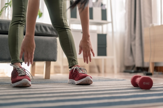 스트레칭을 하는 여성, 그녀는 운동 세션을 위해 워밍업을 하고 있습니다. 운동, 가정 활동에서 운동.