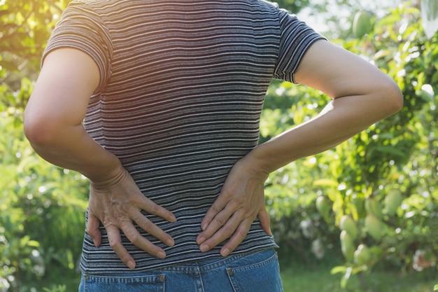 Женщина, страдающая от боли в спине, позвоночника и проблемы с мышцами на открытом воздухе.