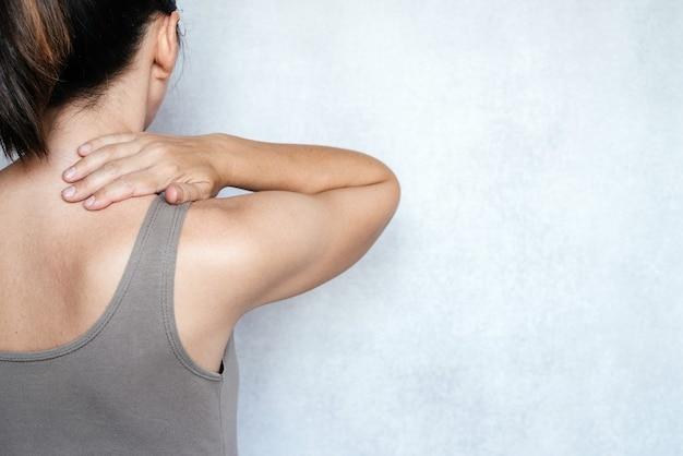 목 통증으로 고통받는 여성과 통증을 완화하기 위해 목을 마사지하는 것, 목 통증을 완화하는 가장 빠른 방법