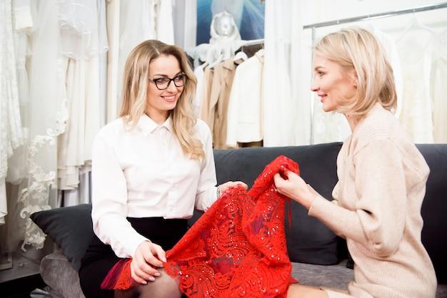 女性の仕立て屋がクライアントと新しいドレスについて話している。