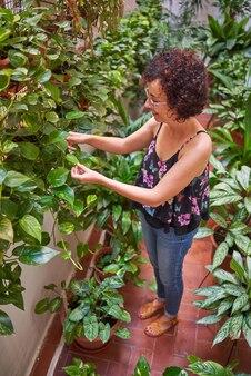 한 여성이 뒤뜰에서 식물을 돌보고 있다