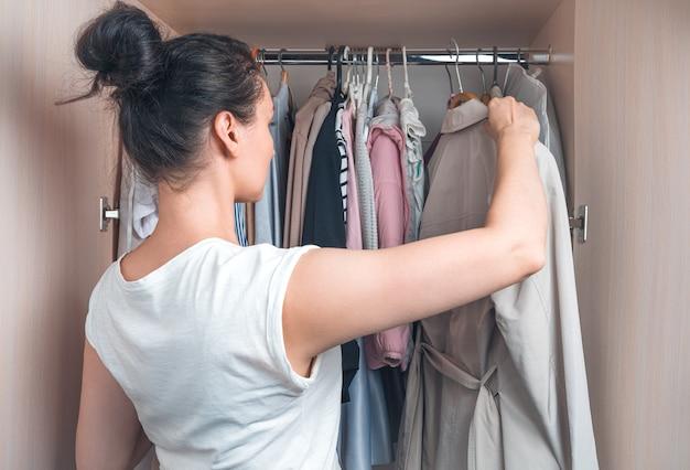 女性がワードローブから服を取り出します。家庭生活の概念。