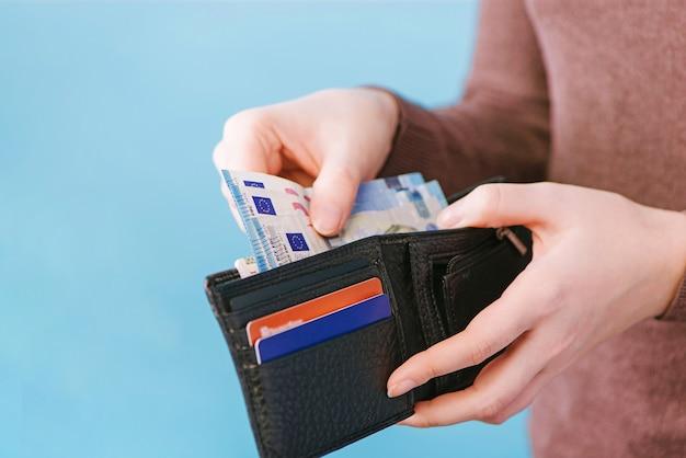 Женщина достает деньги из бумажника на синем фоне с местом для текста. концепция оплаты.