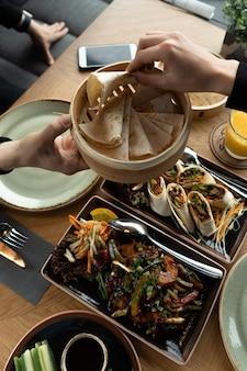 女性は北京ダックのおやつとして男性の手からピタパン、ピタまたはアジアのフラットブレッドを取ります。レストランでの2人での夕食。汎アジアのオリエンタル料理。