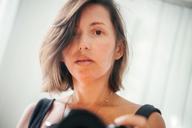 거울 앞에서 dslr 카메라로 셀카를 찍는 여성